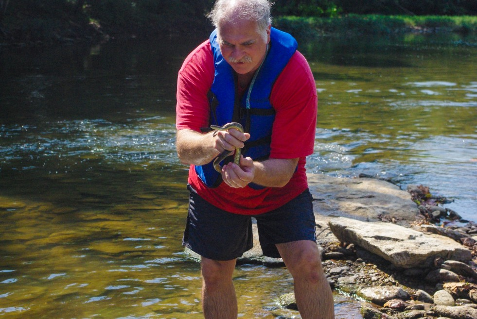 Dr. Phil Short with snake on recent Environmental Club canor trip.
